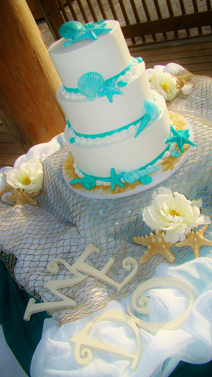 a white wedding cake with bright turquoise starfish and seashells for a bold beach wedding
