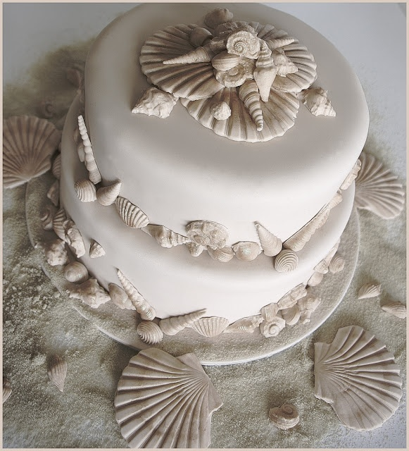 a neutral beach wedding cake with sugar seashells of various kinds looks relaxed and cool