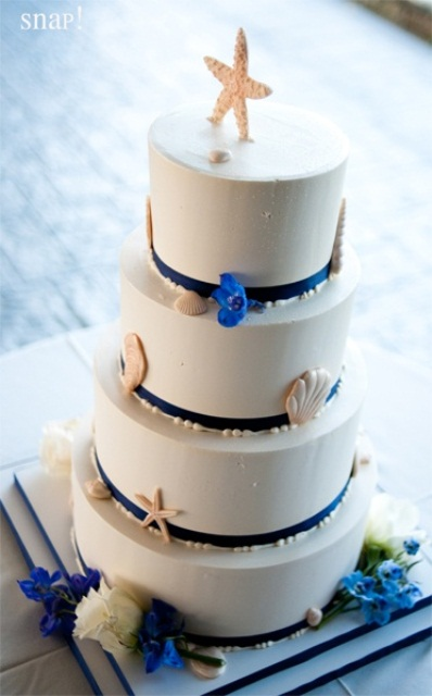 a white wedding cake with navy ribbons, sugar seashells, pearls, blue flowers is amazing for a bold beach or nautical wedding