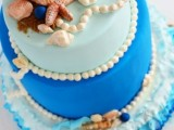 a bright blue color block wedding cake with sugar pearls, starfish, seashells and beach sand is lovely and bold