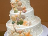 a white shimmering wedding cake with colorful sugar seashells, starfish and pearls is a bold and fun option for a modern beach wedding