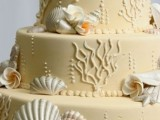 a tan beach wedding cake with coral patterns, pearls, seashells and sugar blooms looks non-typical and the color reminds of beach sand