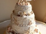 a white patterned beach wedding cake with sugar seashells and starfish, with starfish toppers is a fun and cool wedding cake for a beach wedding