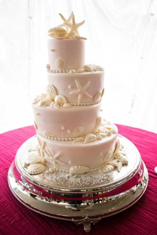 a blush beach wedding cake with sugar starfish, seashells, pearls and other stuff in white is a gorgeous idea for a beach wedding