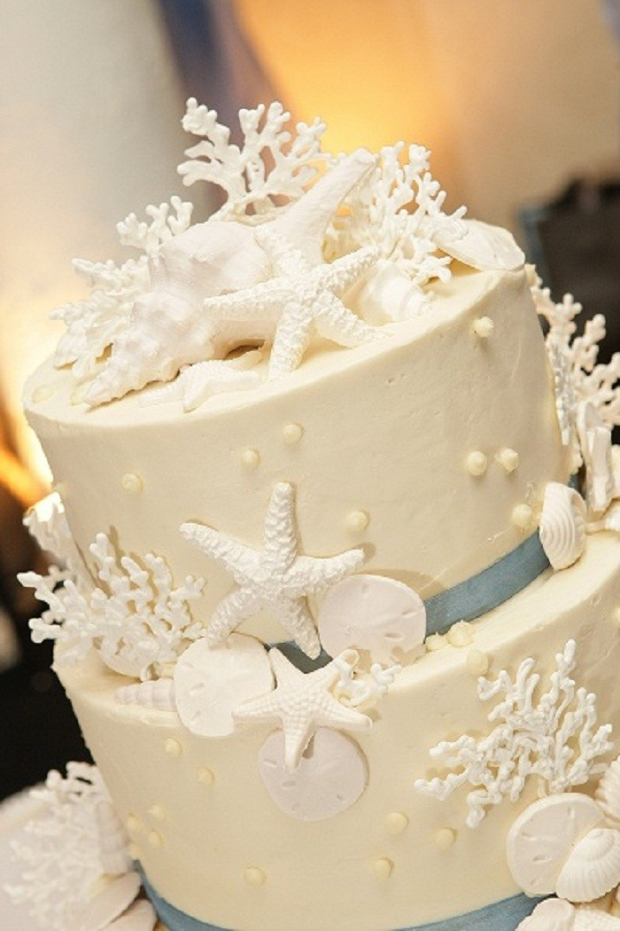a white textural wedding cake with edible pearls, starfish, corals, seashells and ribbons is a classic option for a beach wedding