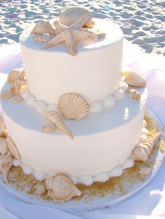 a white beach wedding cake with seashells, of sugar and real ones, and edible pearls