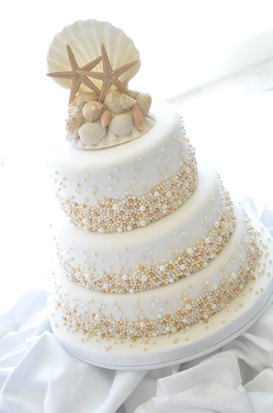 a whimsical beach wedding cake in white, with copper, gold and white pearls attached and sugar seashells and starfish on top