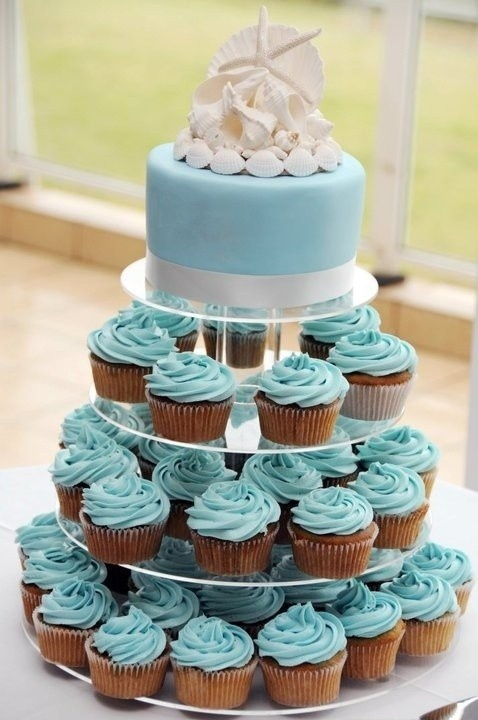 a plain blue wedding cake topped with sugar seashells and matching cupcakes with blue icing for a stylish beach wedding