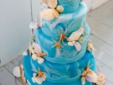 a bright blue watercolor wedding cake with strfish, seashells and pearls is a bold idea for a beach-loving couple