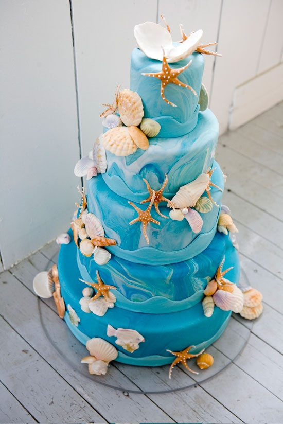 a bright blue watercolor wedding cake with strfish, seashells and pearls is a bold idea for a beach loving couple