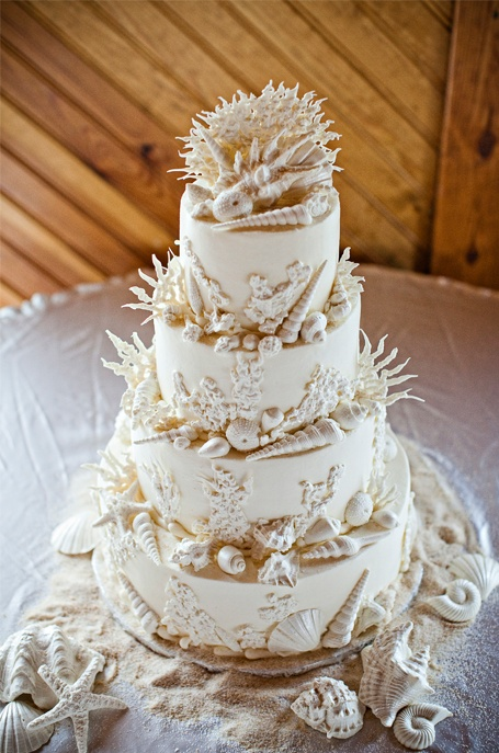 an all white beach wedding cake decorated with seashells, corals and starfish, all made of sugar is lovely and it looks veyr seaside like
