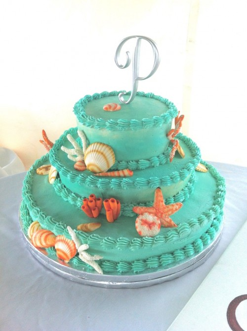 a colorful emerald beach wedding cake with sugar corals, starfish, seashells in red and white is a fun idea