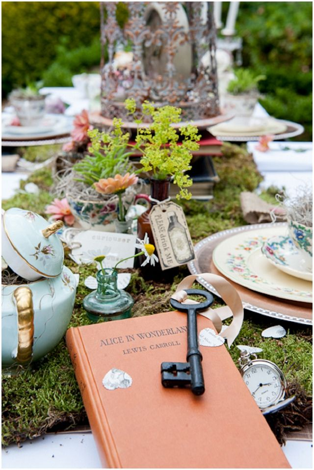 an enchanted forest wedding tablescape with a moss runner, greenery and blooms in vases, teapots and sugar pots with vintage keys