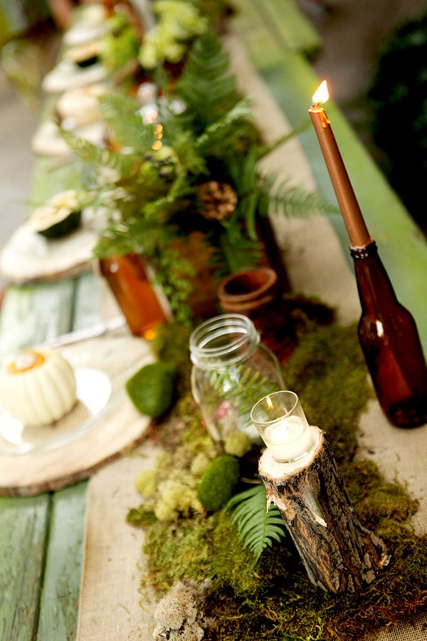 a woodland table runner of moss, candles in glass jars, greenery and ferns for a woodland tablescape