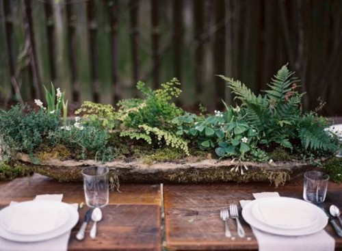 a woodland wedding centerpiece of a rough wooden bowl filled with moss and greenery is a cool and simple idea