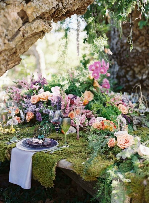a romantic enchanted forest wedding tablescape covered with moss and lush blooms and greenery plus purple glass plates and a neutral napkin