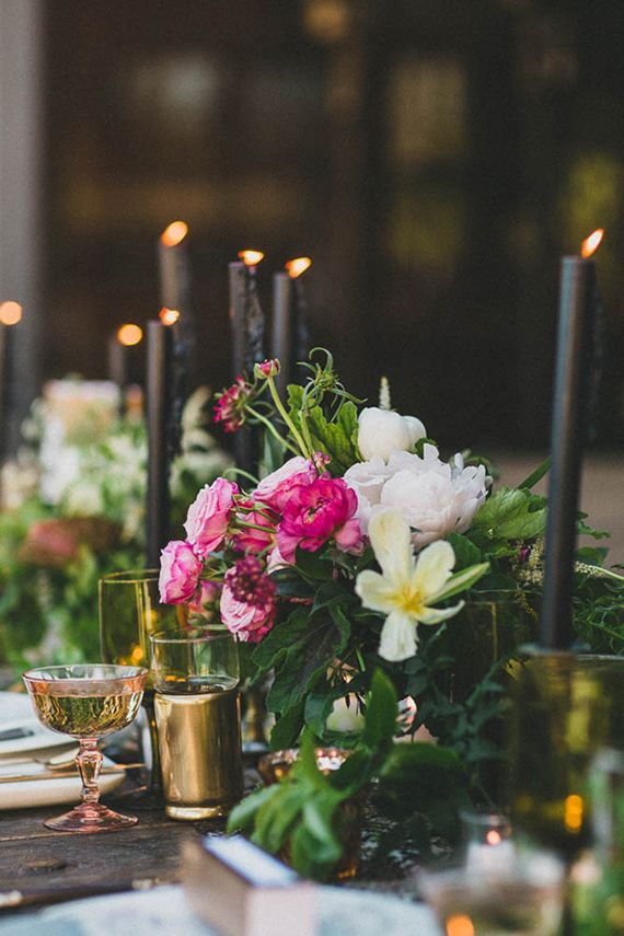a romantic wedding centerpiece of black candles in gold candle holders and lush pink and white blooms
