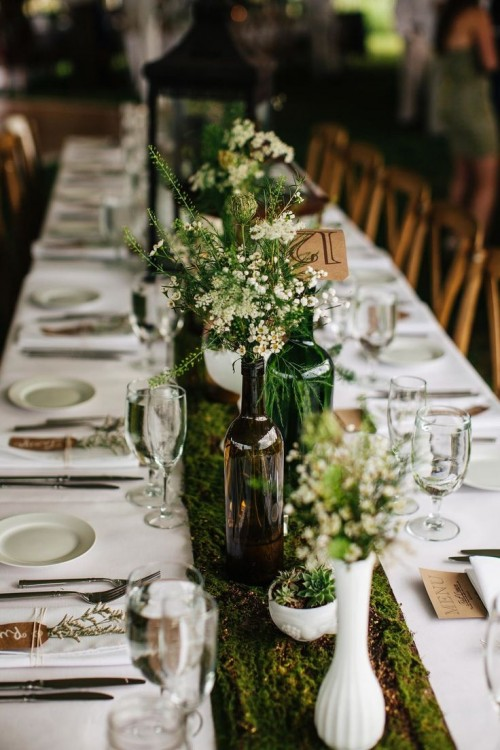 a woodland wedding tablescape with a moss runner, greenery and blooms in vases and tags and blooms for place settings