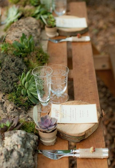 a woodland wedding table runner made of driftwood, moss, rocks and succulents is ideal for a woodland space