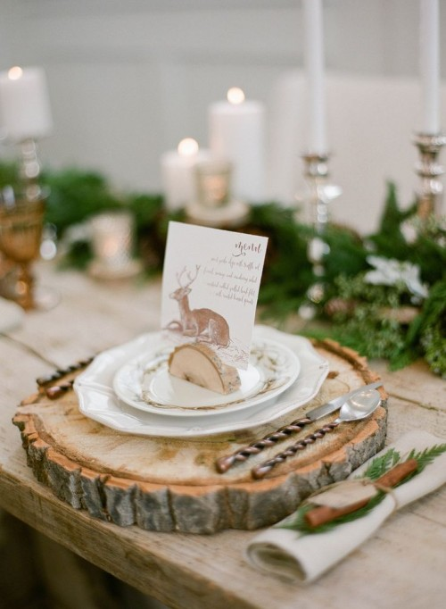 a cozy place setting with a wood slice as a placemat, plates, a card with a deer held by a tree slice