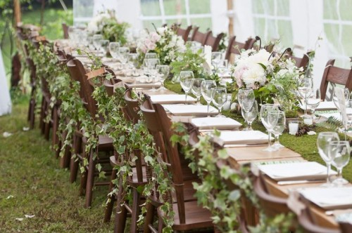 a woodland wedding tablescape with a moss runner, greenery and white blooms in vases and chairs decorated with greenery