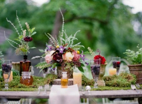 a woodland wedding tablescape with a moss runner, bold blooms and greenery and feathers for decor