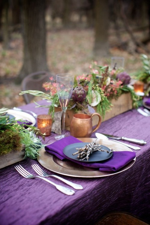 a bright tablescape with woodland touches - twigs, wooden planters with greenery and artichokes plus moss