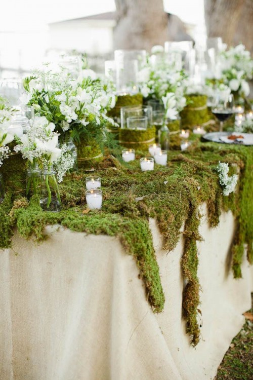 a spring woodland wedding tablescape with a moss tablecloth, fresh white blooms and lots of candles