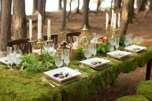 a woodland wedding tablescape with a moss tablecloth, greenery, candles in gold candleholders and an elegant clock