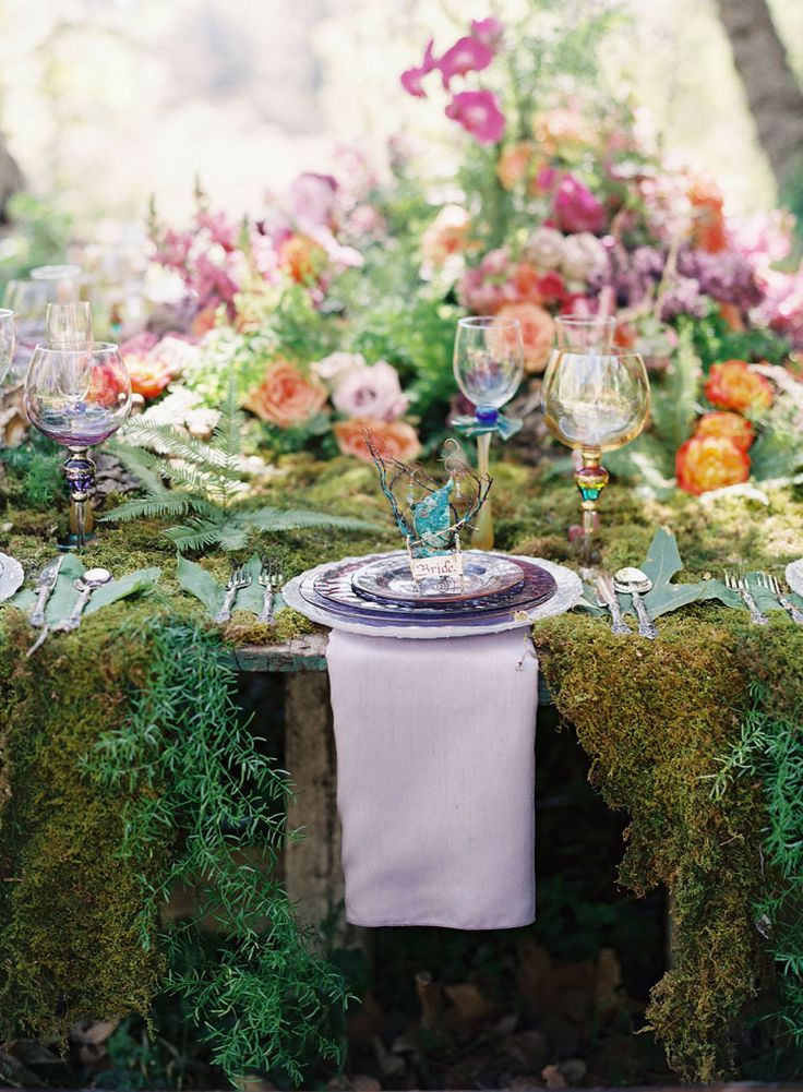 a lush forest wedding table setting with a moss tablecloth, lush blooms and ferns