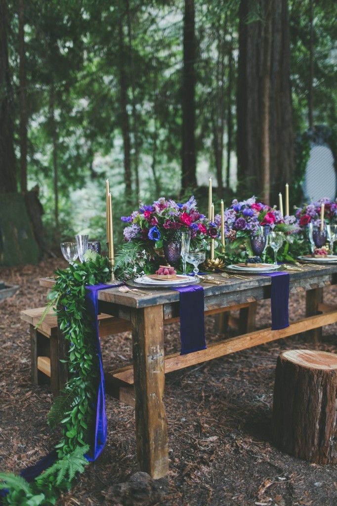 a bold woodland wedding tablescape with jewel toned blooms, a greenery runner and purple napkins