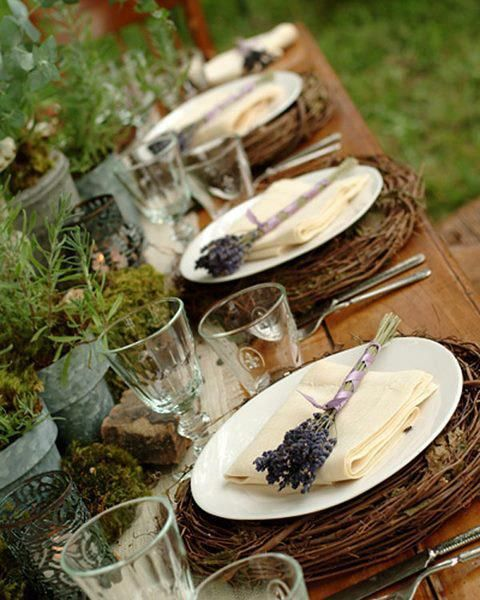 a wedding tablescape of twiggy placemats, moss, greenery, rocks and colored glasses plus lavender