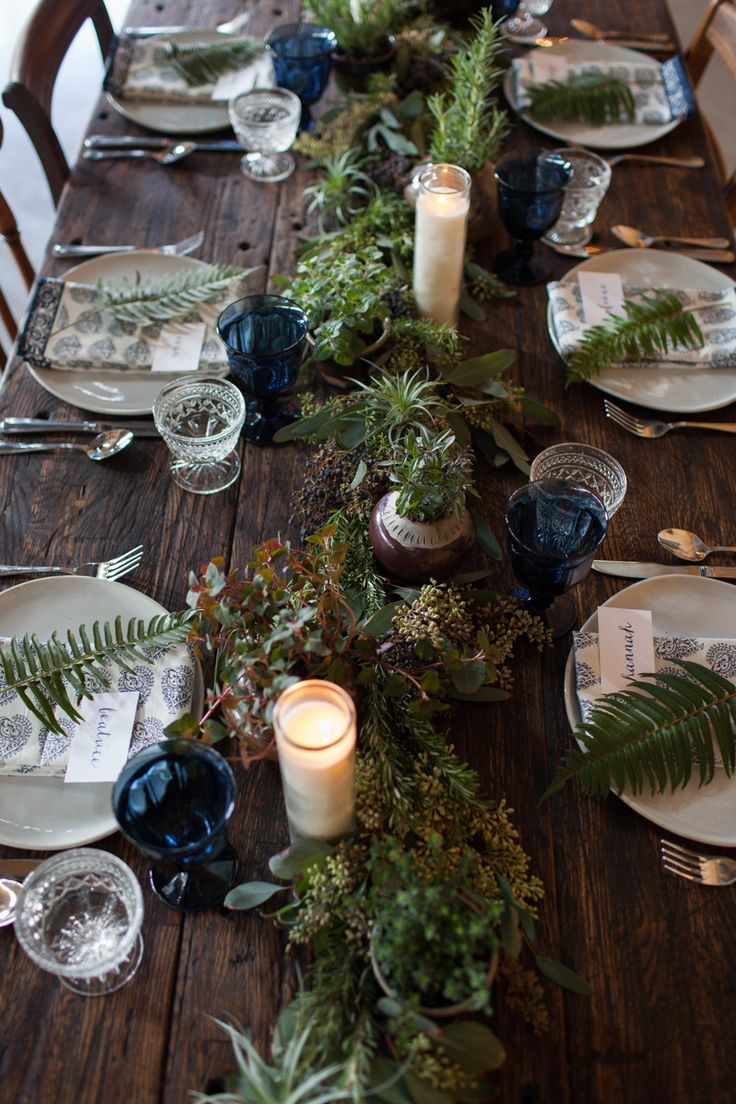 a simple woodland tablescape with an uncovered table, a textural greenery table runner, blue glasses and ferns on each place setting