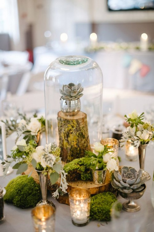a glam woodland wedding centerpiece with moss, wood slices, blooms, a tree stump with a succulent in a cloche