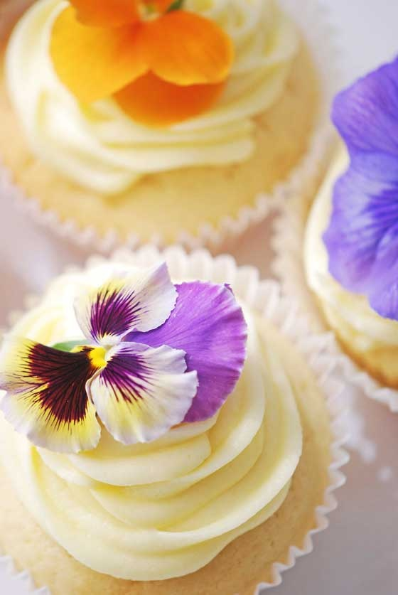 wedding cupcakes with vanilla frosting and pansies look bright, chic and very summer like