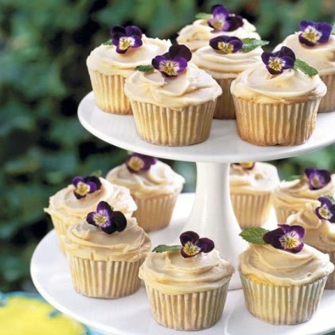 wedding cupcakes with vanilla frosting and violets are gorgeous wedding desserts for spring and summer celebrations