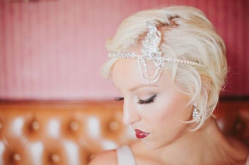 an art deco bridal headpiece of rhinestones and an embellished feather is a lovely and bold accent