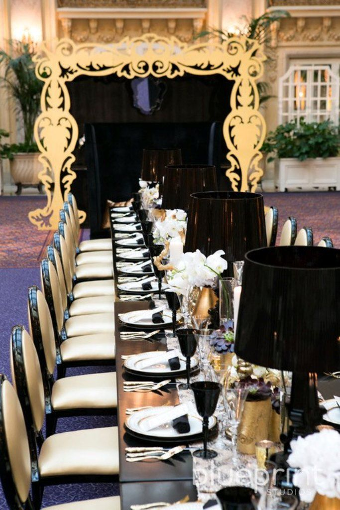 a refined black, gold and white wedding tablescape with black lamps, gold vases with white blooms and black glasses