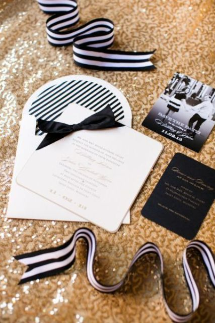black and white wedidng stationery suite placed ona  gold sequin backdrop to show off the wedding color scheme