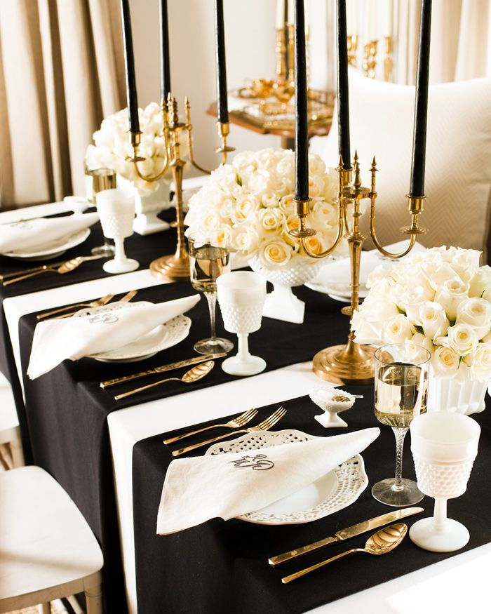 a refined black, white and gold wedding table setting with lush white rose centerpieces