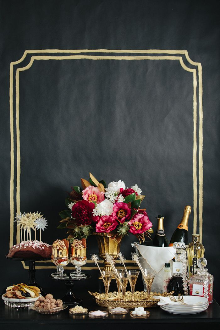 a black and gold backdrop, gold vases and glasses