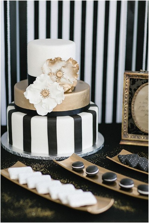 a gold and striped black and white wedding cake with sugar blooms
