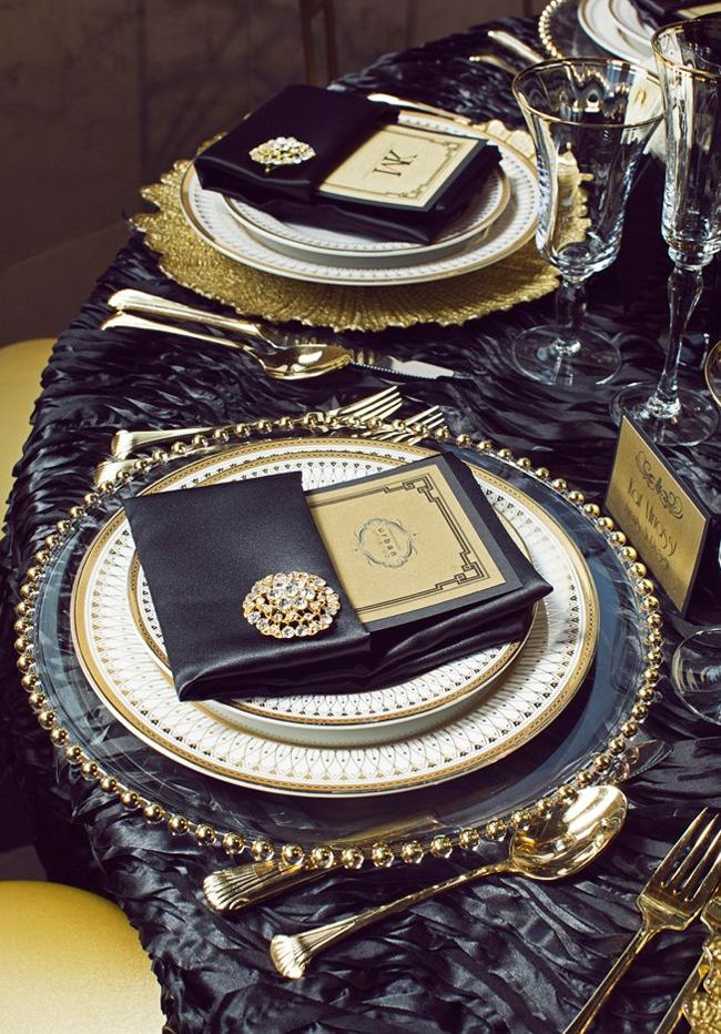 a very elegant and refined wedding tablescape with gold cutlery and brooches