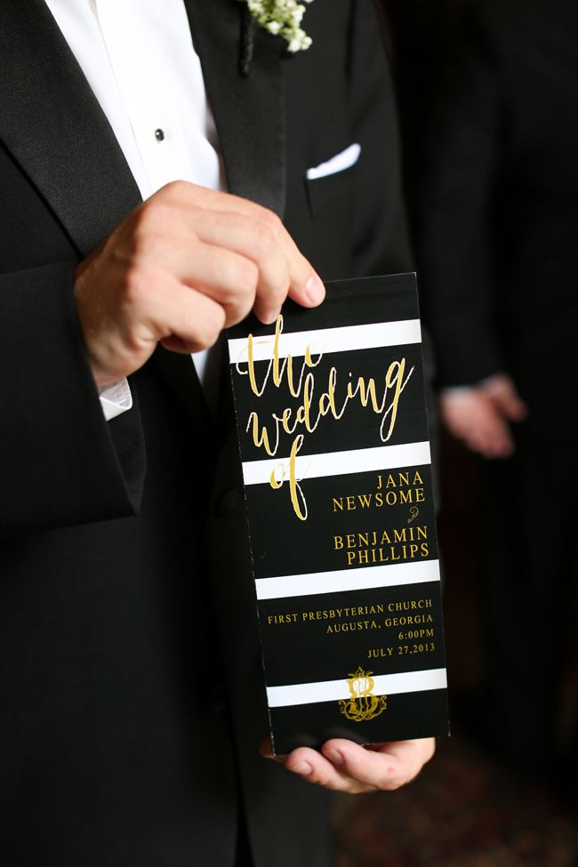 a striped black and white wedding invitation with gold calligraphy