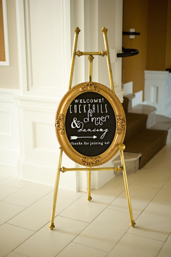 a black chalkboard wedding sign with a gold frame