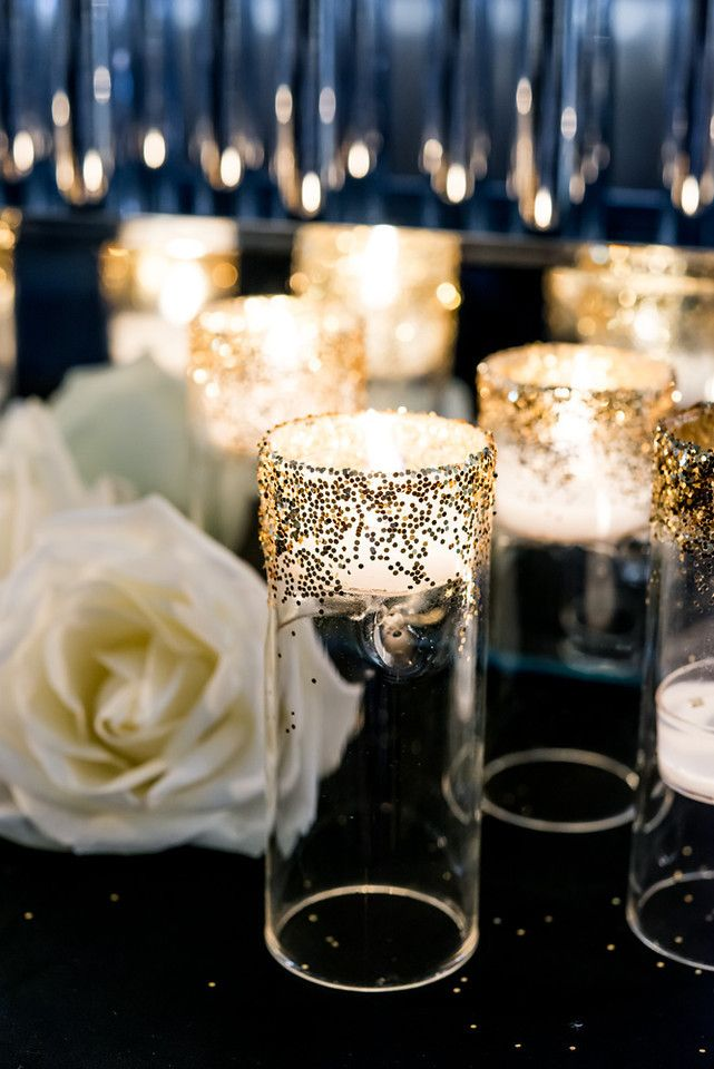 a black tablecloth and sparkling candle holders plus white roses for table decor