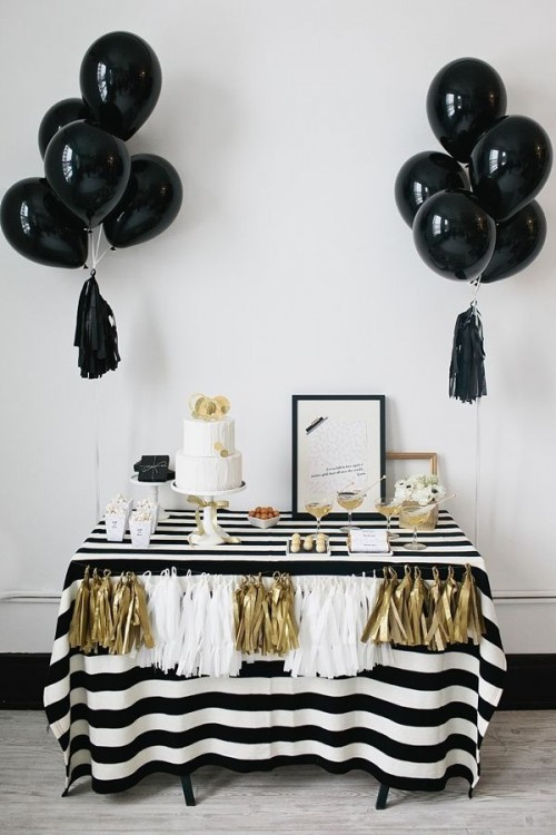 a black, white and gold wedding dessert table with balloons and tassels, with a striped tablecloth and tasssel garlands