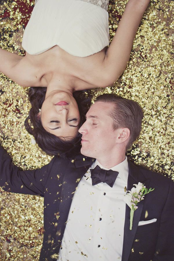 a groom wearing a black tux and a gold sequin backdrop for the wedding portraits