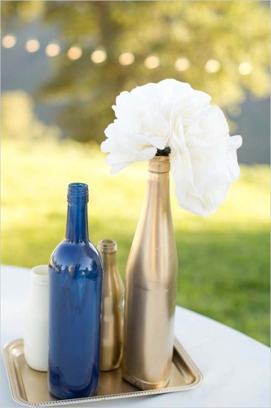 navy and gold bottle vases with white blooms for decor