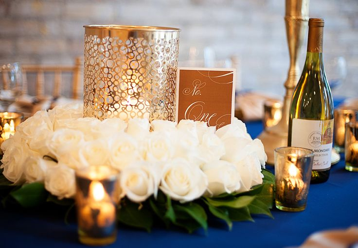 a navy, white and gold wedding table setting with lush blooms, candle holders and bottles